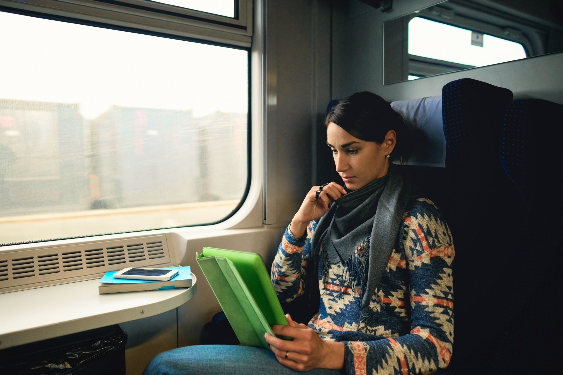 A woman using her Tap with her tablet while riding the train