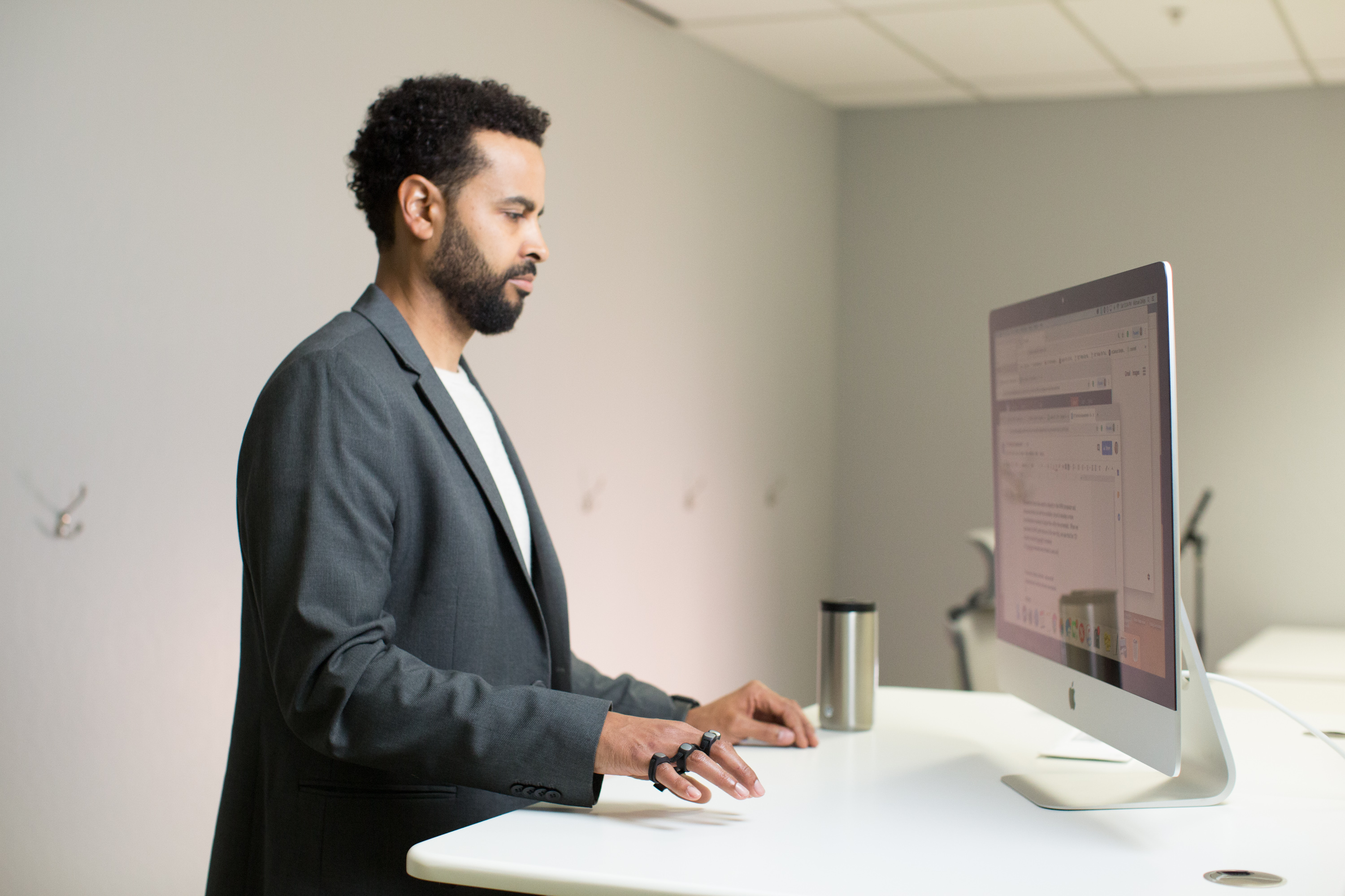 Man tapping at standing desk with perfect posture using Tap